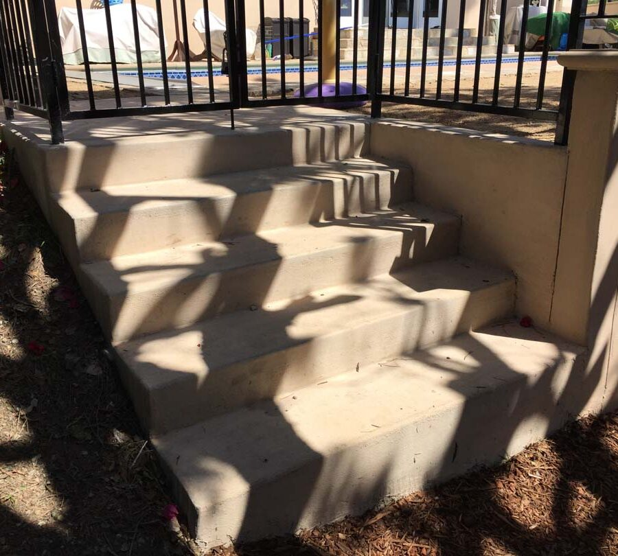 New colored concrete steps and fence over a new retaining wall. Pacificland Constructors