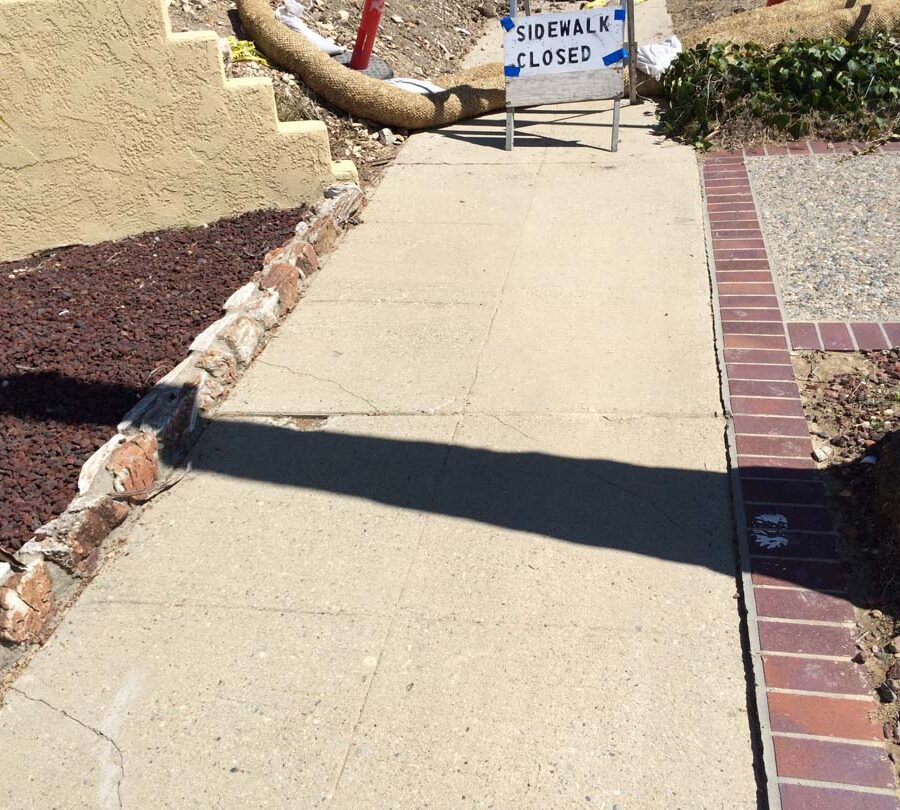 Old cracked and uneven concrete sidewalk. Pacificland Constructors