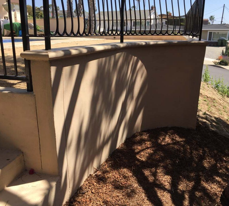 New colored concrete steps and fence over a new retaining wall with concrete precast wall cap. Pacificland Constructors