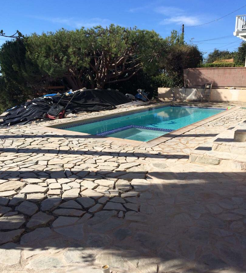 Old flagstone pool deck yet the existing flagstone still under construction. Pacificland Constructors