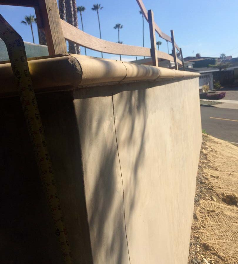 Construction of a new retaining wall with a colored concrete precast. Pacificland Constructors