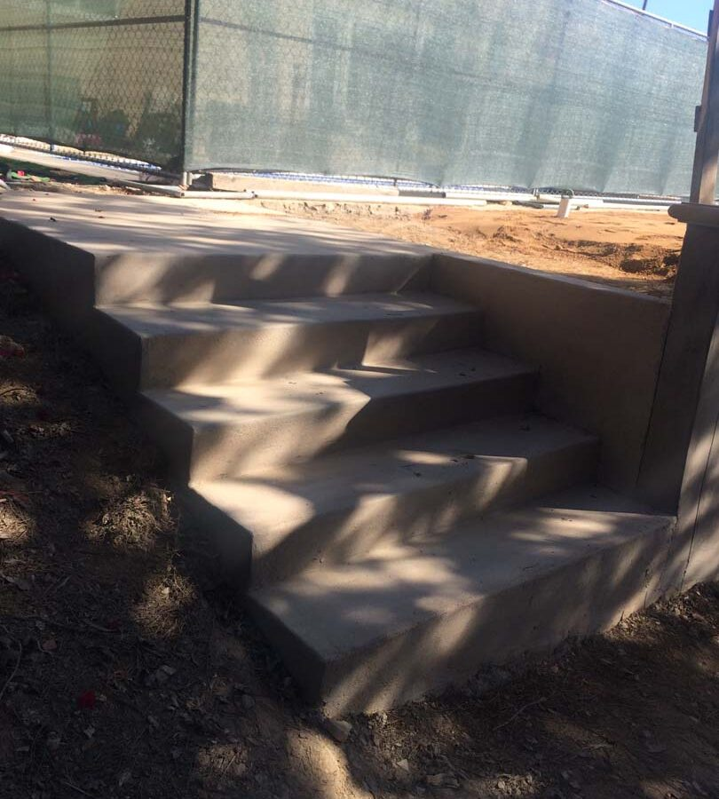 Construction of new steps leading to the elevated backyard patio held up by a retaining wall. Pacificland Constructors