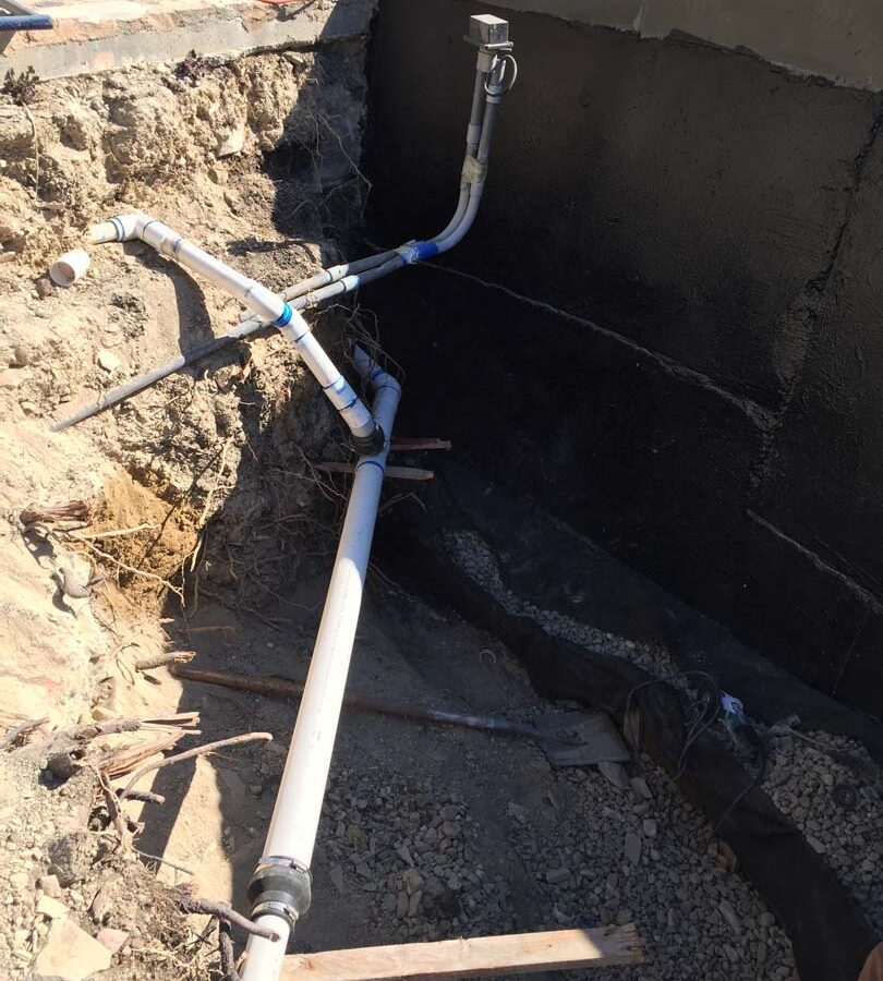 Waterproofing and pipe drainage that is buried is being compacted in place. New electrical pipe connections shown will also be buried out of sight. Pacificland Constructors