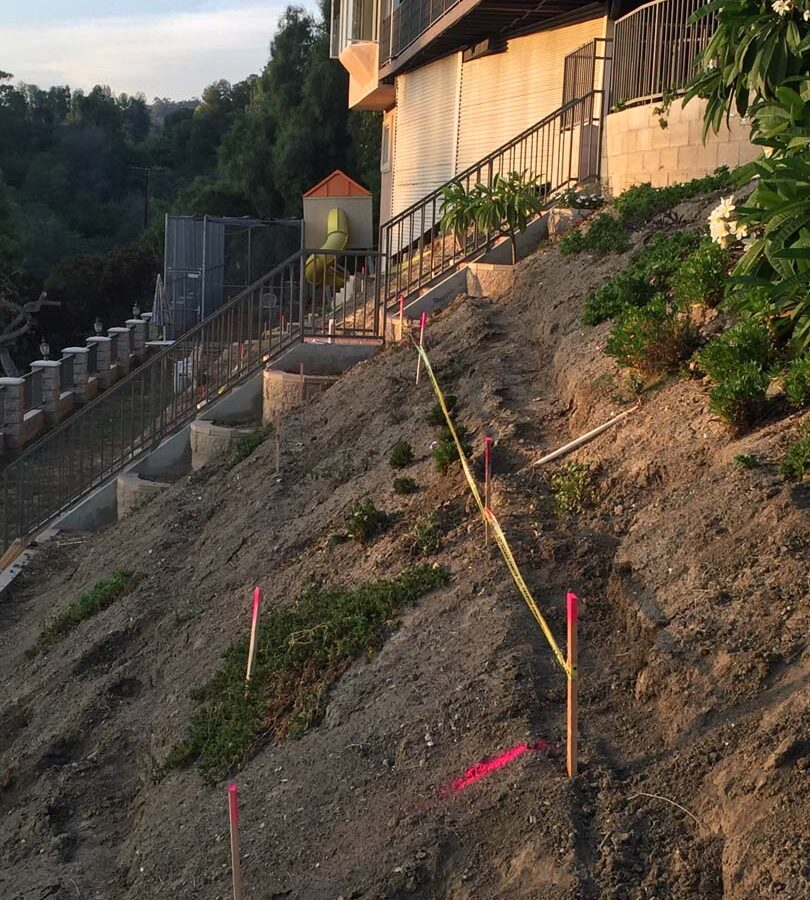 Construction of a new retaining wall long the slope of the hill. Pacificland Constructors