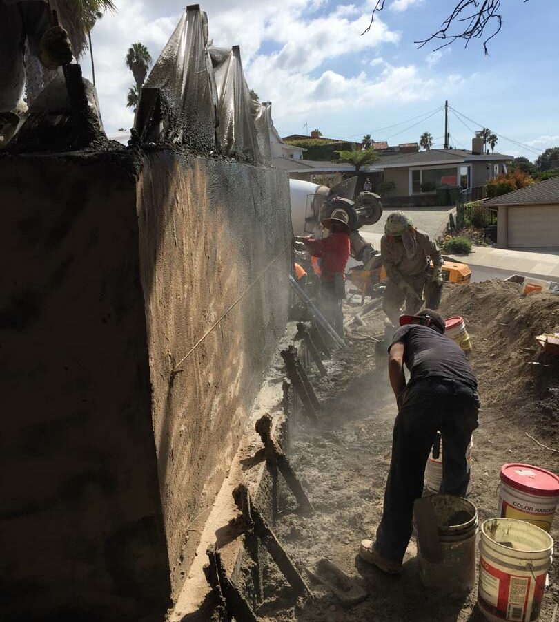Construction of a new retaining wall shotcrete shooting, leveling, and color staining. Pacificland Constructors