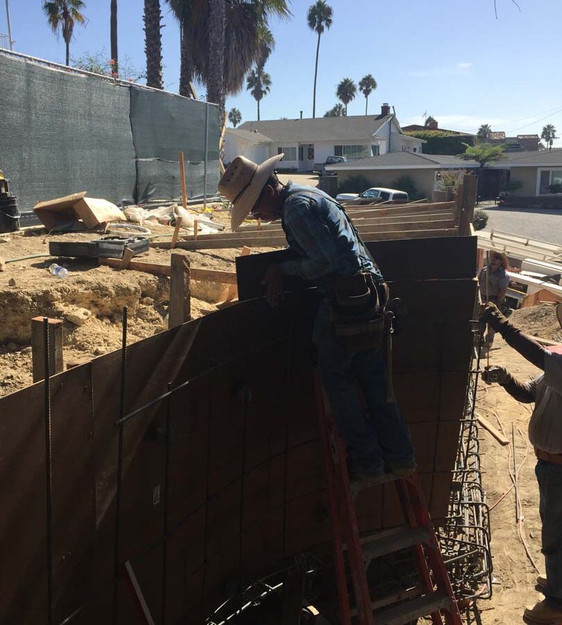 Construction of a new retaining wall steel rebar reinforcement. Pacificland Constructors
