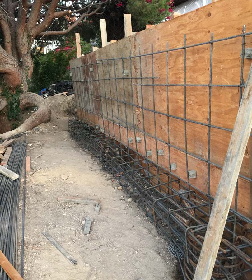 Construction of a new retaining wall steel rebar reinforcement for grade beam and retaining wall. Pacificland Constructors