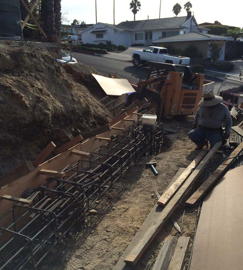 Construction of a new retaining wall steel rebar reinforcement for grade beam and formwork for the retaining wall. Pacificland Constructors