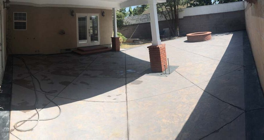New stamped concrete with dark concrete ribbons and brick veneer columns. Pacificland Constructors
