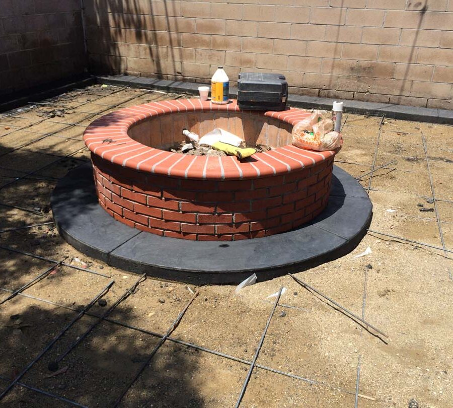 Construction of a new Brick fire pit and dark concrete ribbon for a home. Pacificland Constructors