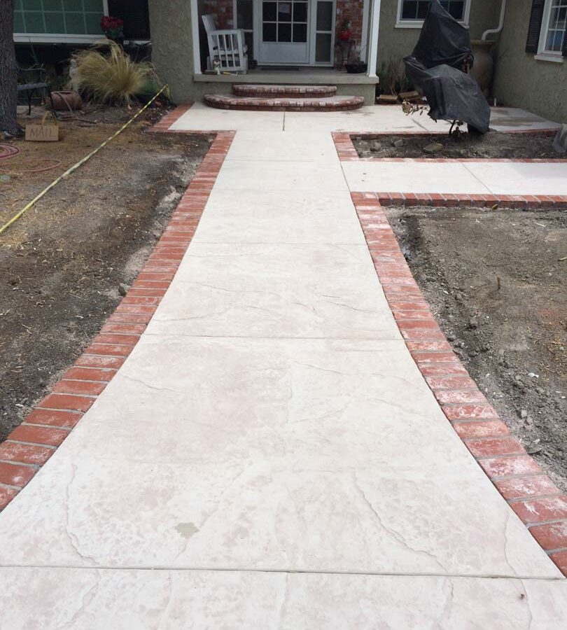 New stamped concrete front patio with brick ribbon with manufactured white stained brick ribbons and steps that creates a vintage look. Pacificland Constructors