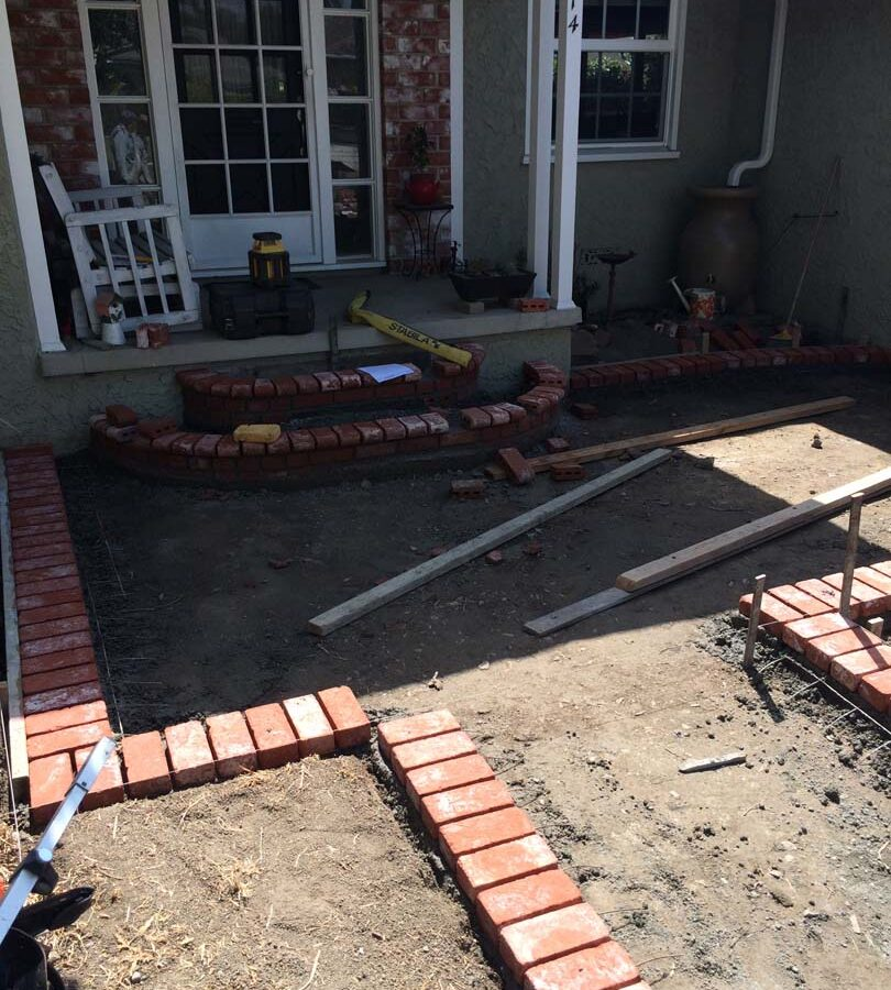 Construction of new front patio with brick ribbons that are manufactured white stains that will create a vintage look. Pacificland Constructors
