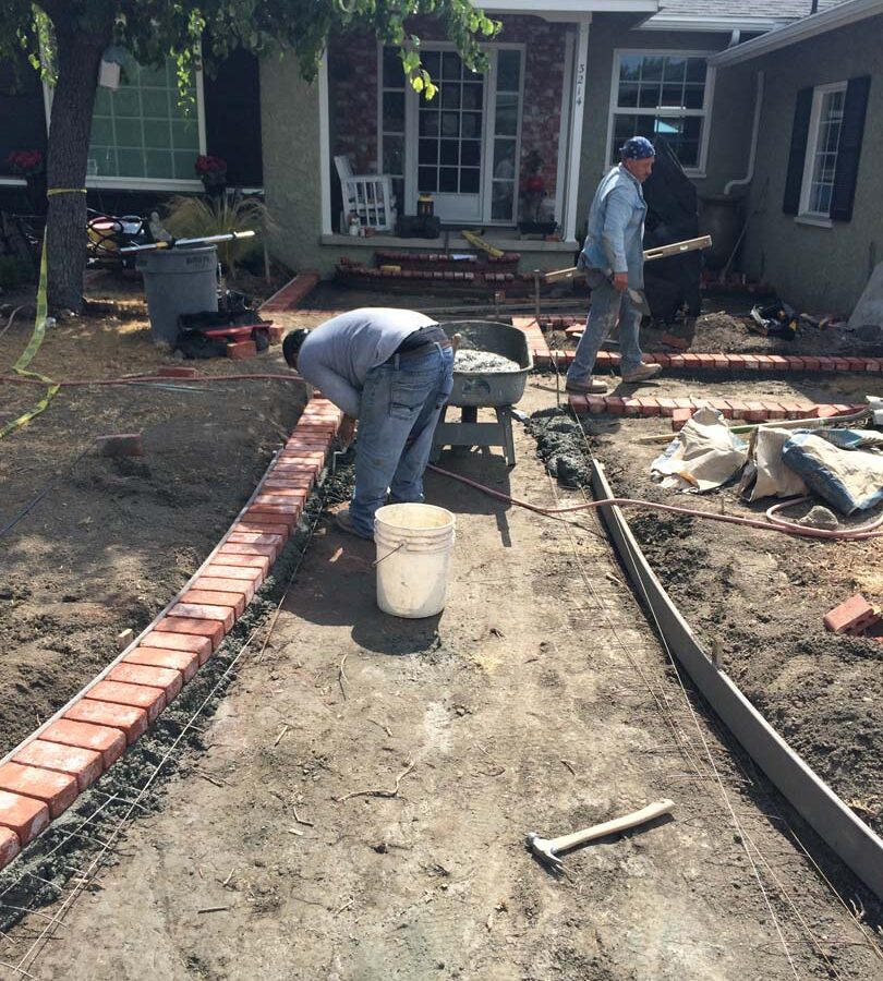 Construction of a new stamped concrete walkway with brick ribbons that are manufactured white stains to create a vintage look. Pacificland Constructors