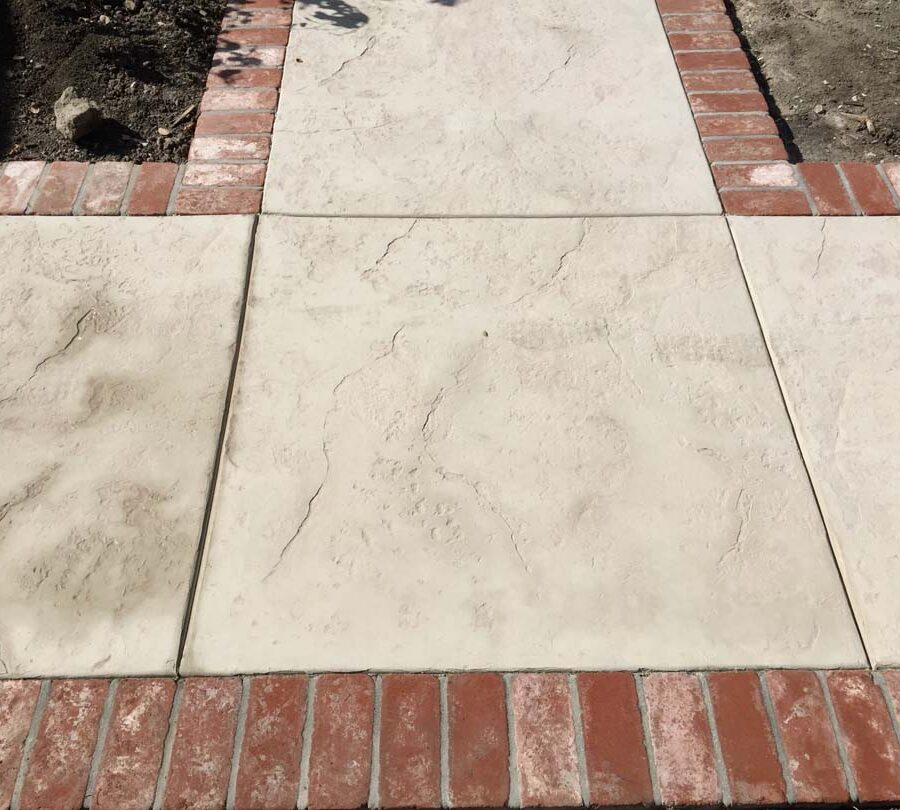 Colored stamped concrete with brick ribbons and handmade joints.