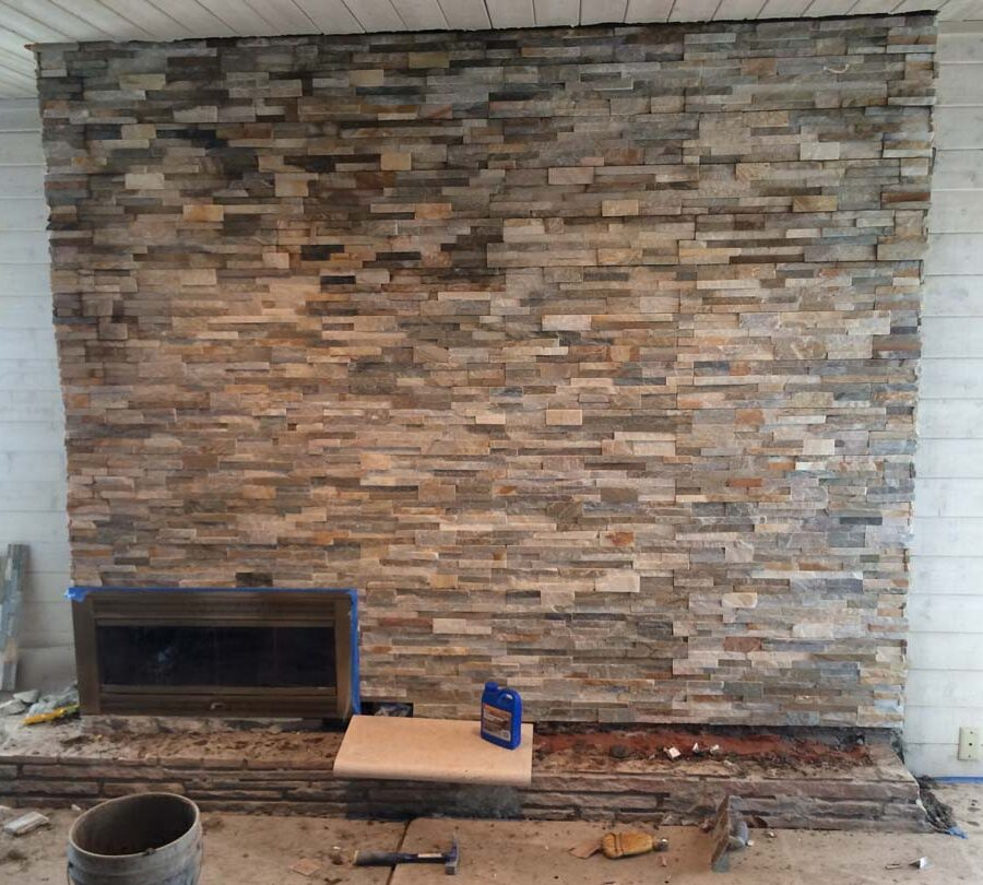 Construction of stone veneer for a chimney. This creates a great natural and relaxing theme for this home's living room.