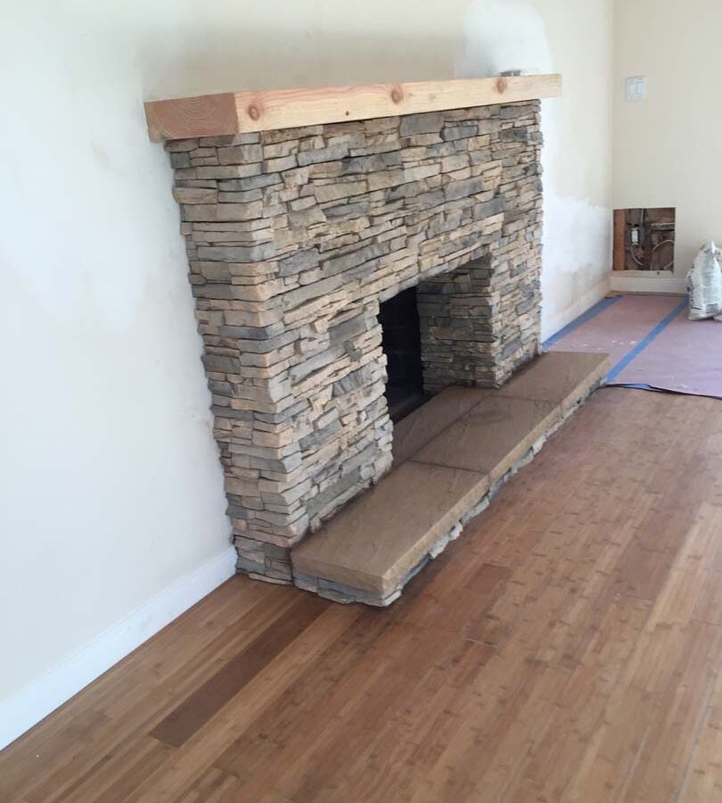 New stone veneer over the existing fireplace to create a vintage theme for the home. Pacificland Constructors