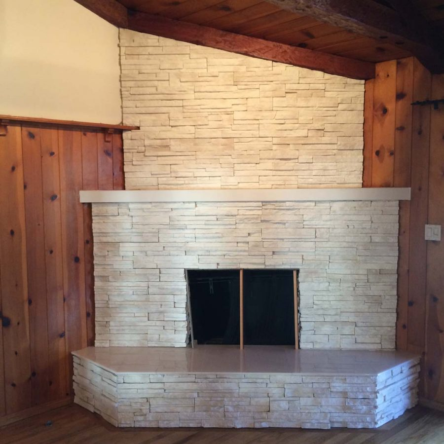 This white stone veneer fireplace with a marble/granite outer hearth will warm up the home during the winter holidays. Pacificland Constructors