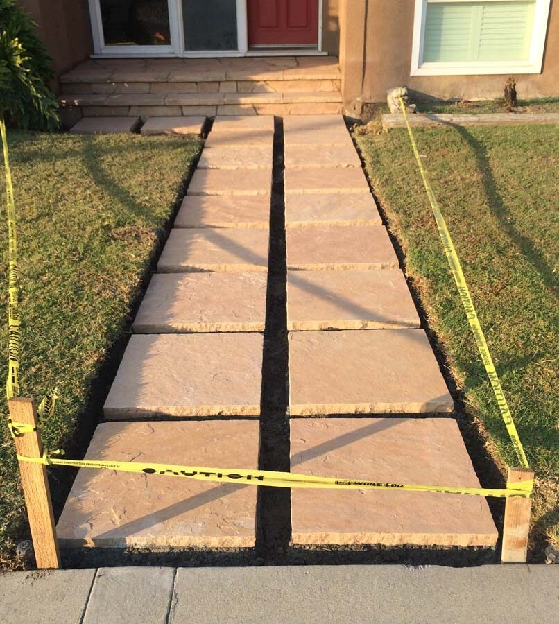 Custom stone cut slabs used as a walkway for a home's entrance. Pacificland Constructors