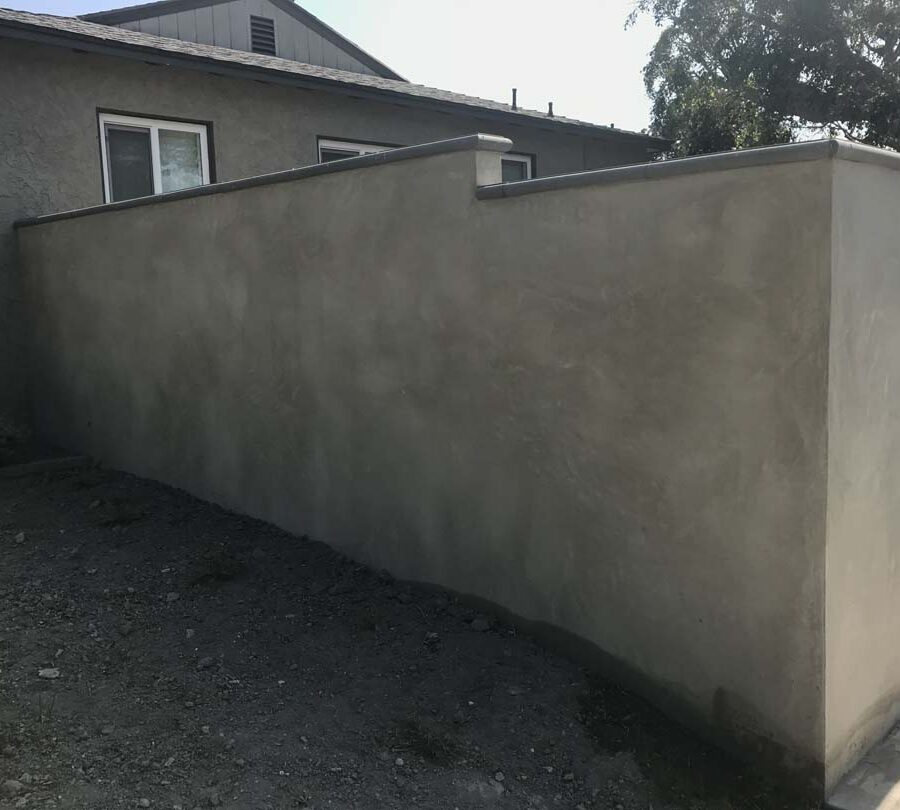 CMU block wall with a smooth stucco finish topped off with stepstone caps. Pacificland Constructors