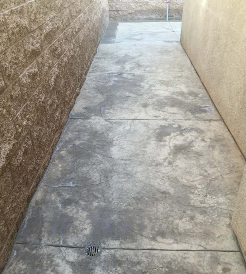 Gray stamped concrete and new CMU tan split face block wall. Pacificland Constructors