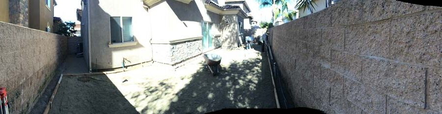 Panoramic view of the construction for a new colored stamped concrete backyard in Bellflower, CA. Pacificland Constructors