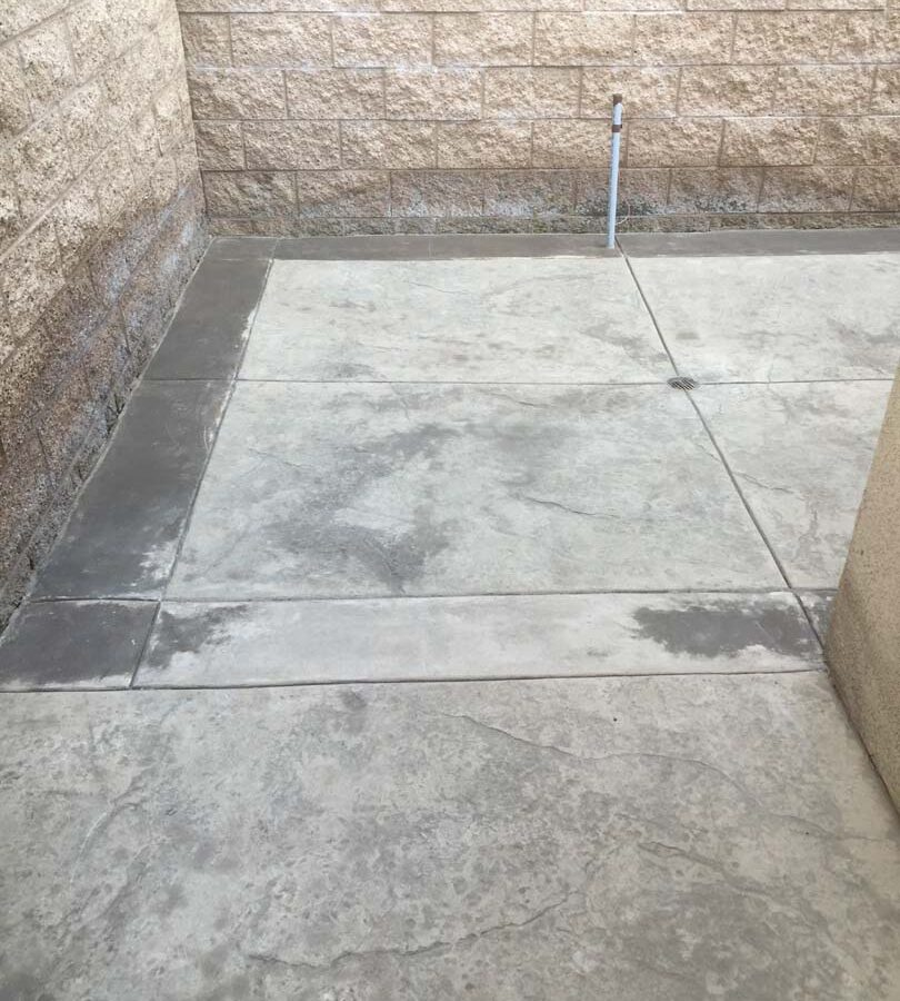 Gray stamped concrete with soffcut joints, a darker colored concrete ribbon, and a new CMU split faced block wall along the property perimeter. Pacificland Constructors