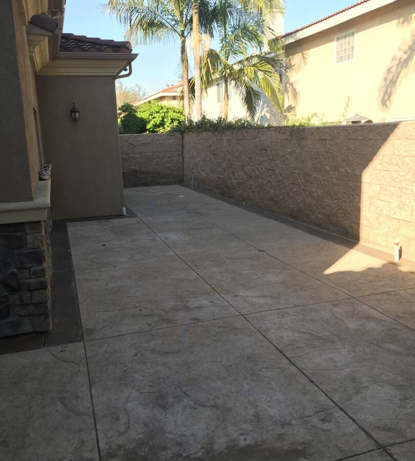 Gray stamped concrete with soffcut joints, a darker colored concrete ribbon, and a stone veneer for the backyard. Pacificland Constructors