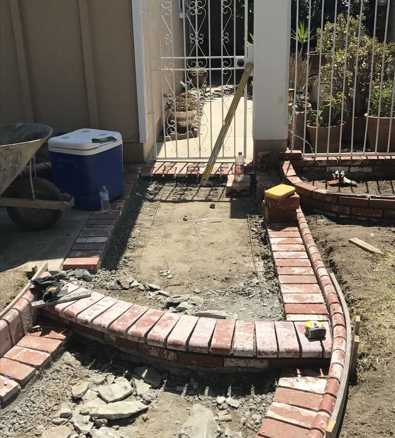 Construction of a new beautiful curved front yard concrete walkway with brick ribbon bull-nosed steps. Pacificland Constructors