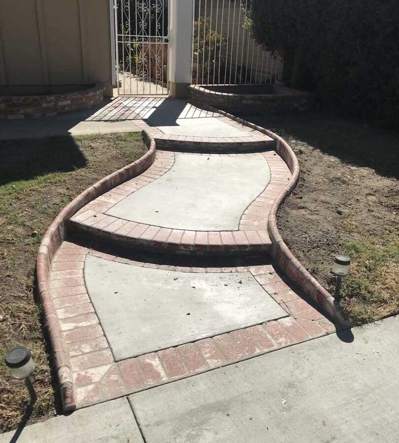 New beautiful curved front yard concrete walkway and steps with brick ribbon and bull-nosed steps. Pacificland Constructors
