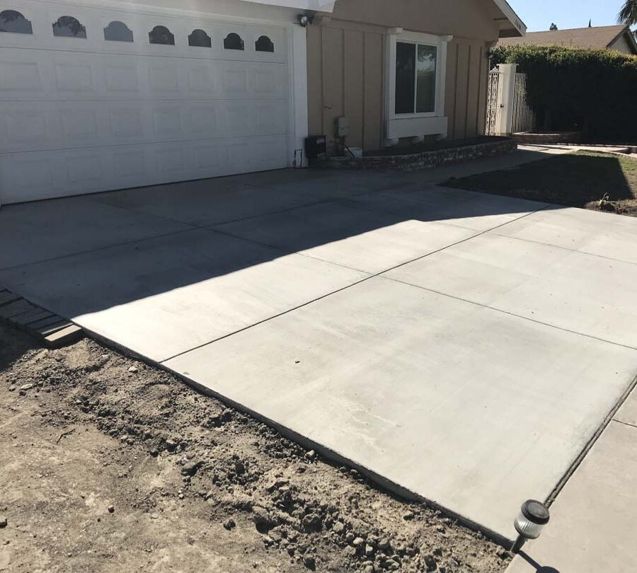 New broom swept concrete driveway with hand scorched joints. Concrete will always crack. These hand scorched joints are intended to control these cracks in a manner that the slab still keeps its cosmetic and structural integrity. Pacificland Constructors