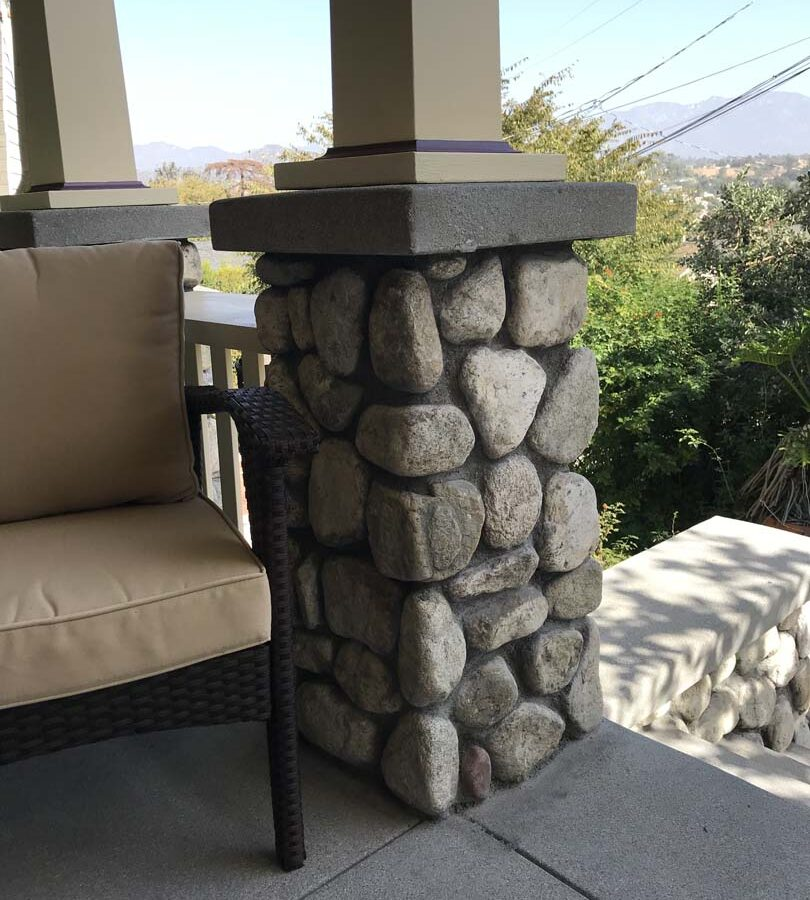Cobble stone covered short wall topped off with a concrete poured wall cap. Pacificland Constructors