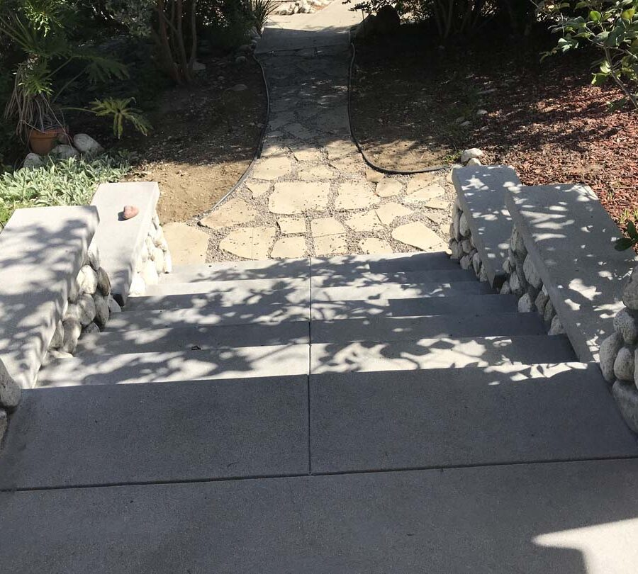 Cobble stone covered short wall topped off with a concrete poured wall cap. New concrete steps have a broom finish texture and a flagstone walkway. Pacificland Constructors