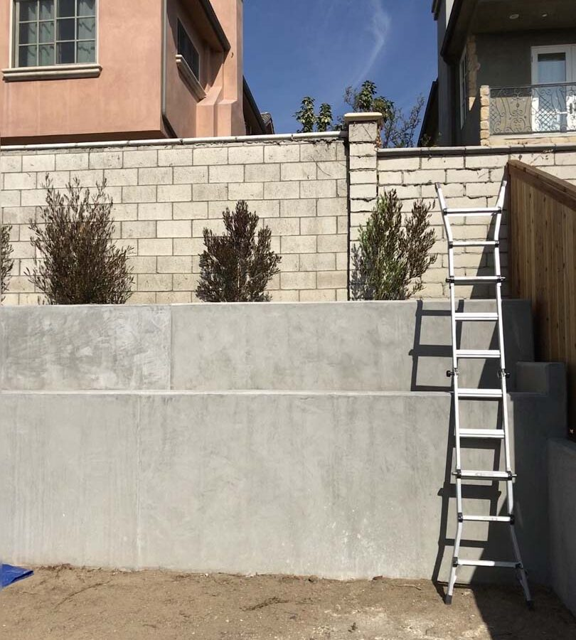 New pour in place concrete retaining wall for a backyard in Huntington Beach, CA. This retaining wall creates more flat area for the home because it holds up the differential earth elevation from the neighbor's home. Pacificland Constructors