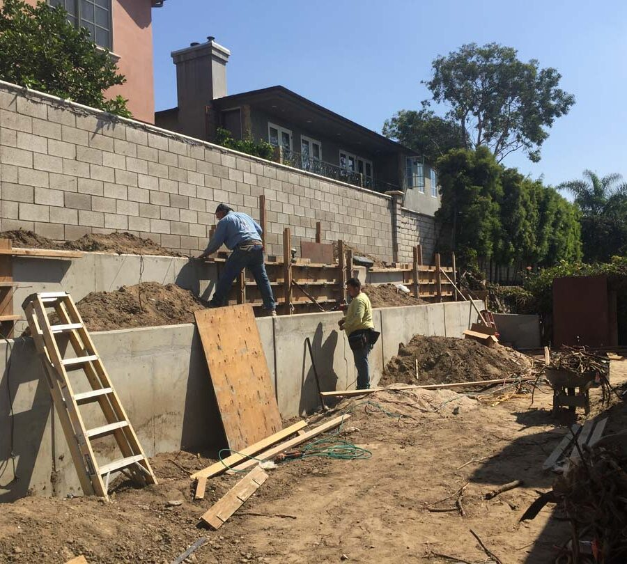 Construction of a new concrete retaining wall for a backyard in Huntington Beach, CA. Here Pacificland is stripping off the forms off the poured in place concrete retaining walls. Pacificland Constructors