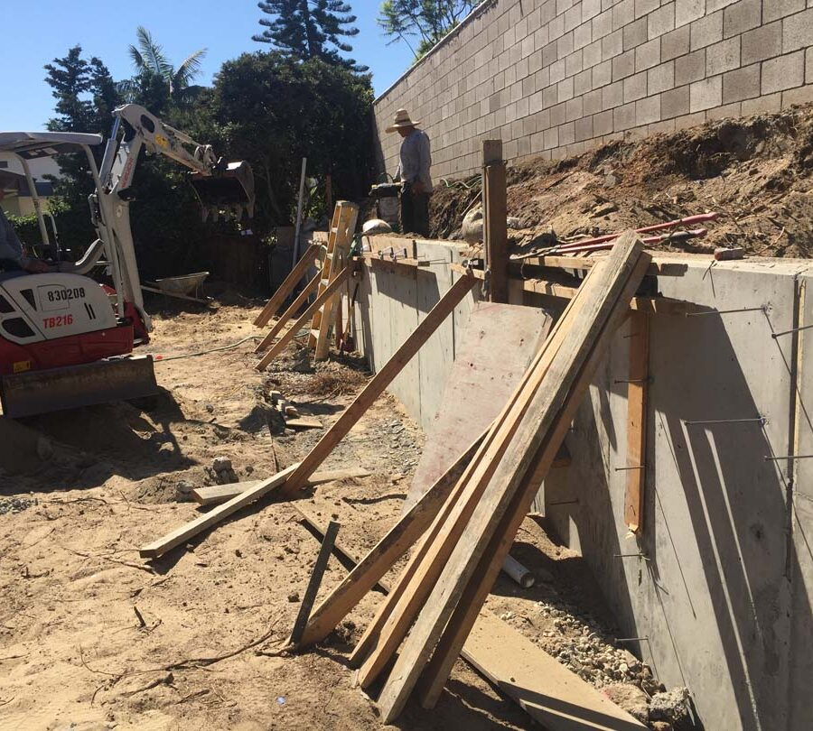 Stripping the formwork carpentry from this new concrete retaining wall for a backyard after pouring it. Pacificland Constructors