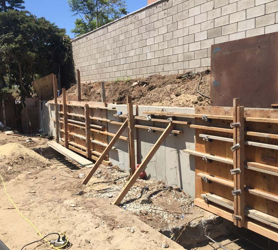 Formwork carpentry and reinforcement for a new concrete retaining wall for a backyard in Huntington Beach, CA. Pacificland Constructors