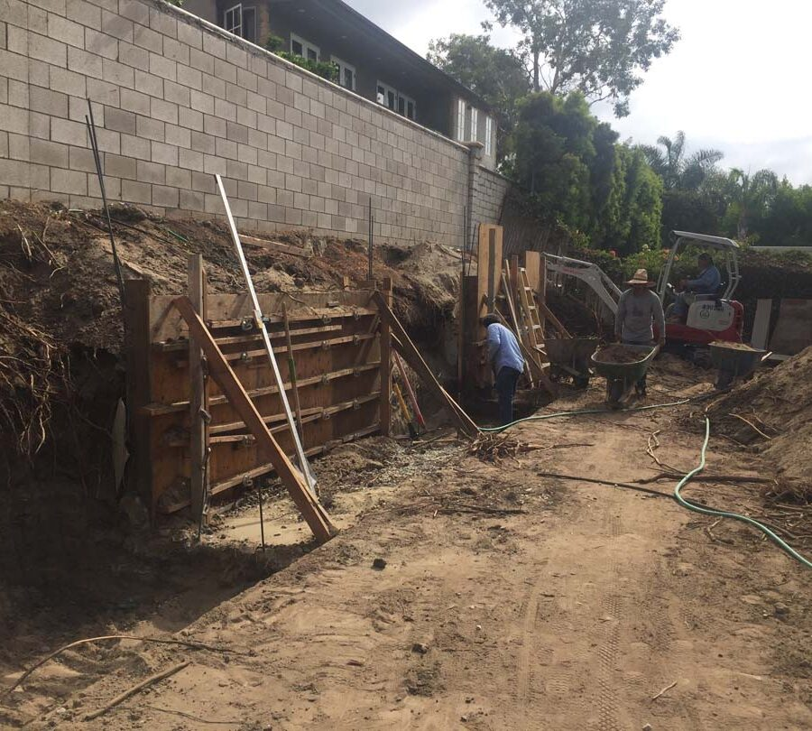 Formwork carpentry and steel reinforcement for a new concrete retaining wall for a backyard in Huntington Beach, CA. Pacificland Constructors