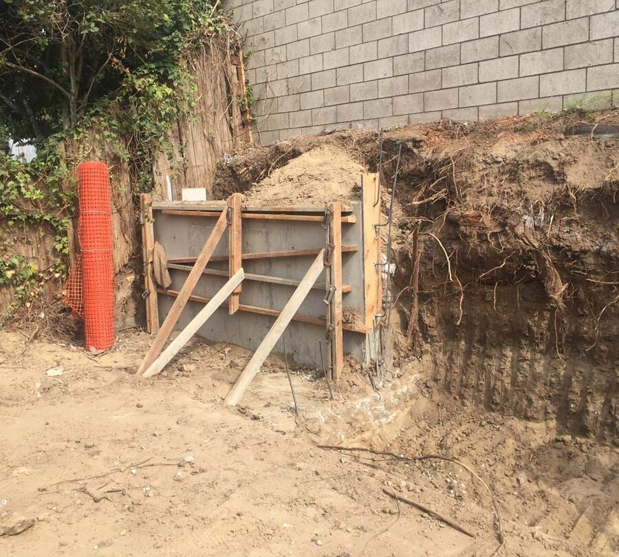 Excavating for a new section of concrete retaining wall. This must be done in sections to avoid having the uneven soil collapse. Pacificland Constructors