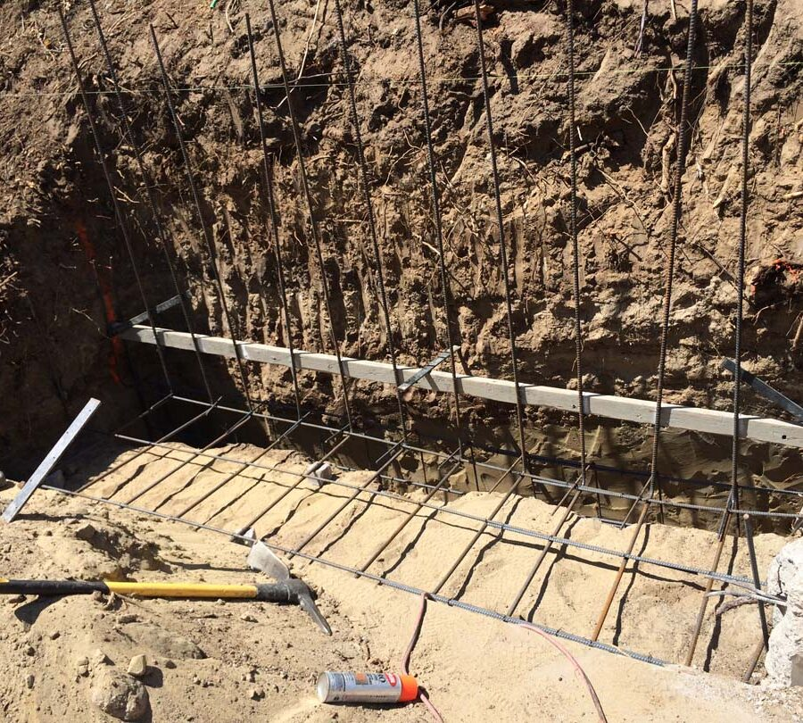 Reinforcement of strip footings with steel ironwork for a new section of concrete retaining wall. Pacificland Constructors