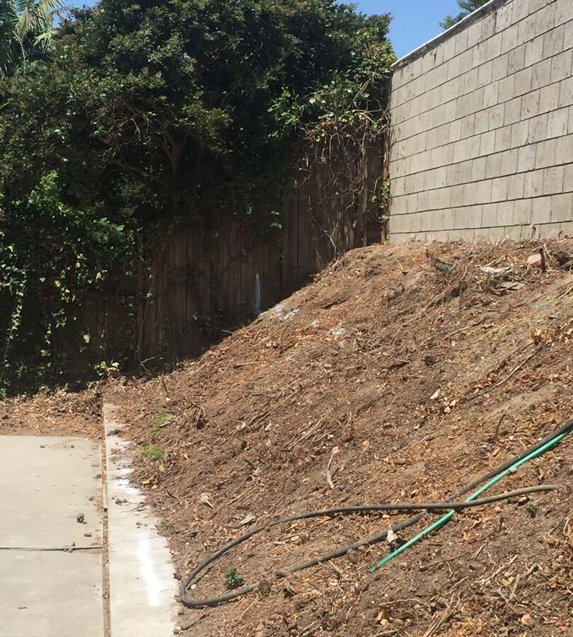 Old sloped hill where a new retaining wall will be built to create more flatspace in the backyard and safety. Pacificland Constructors
