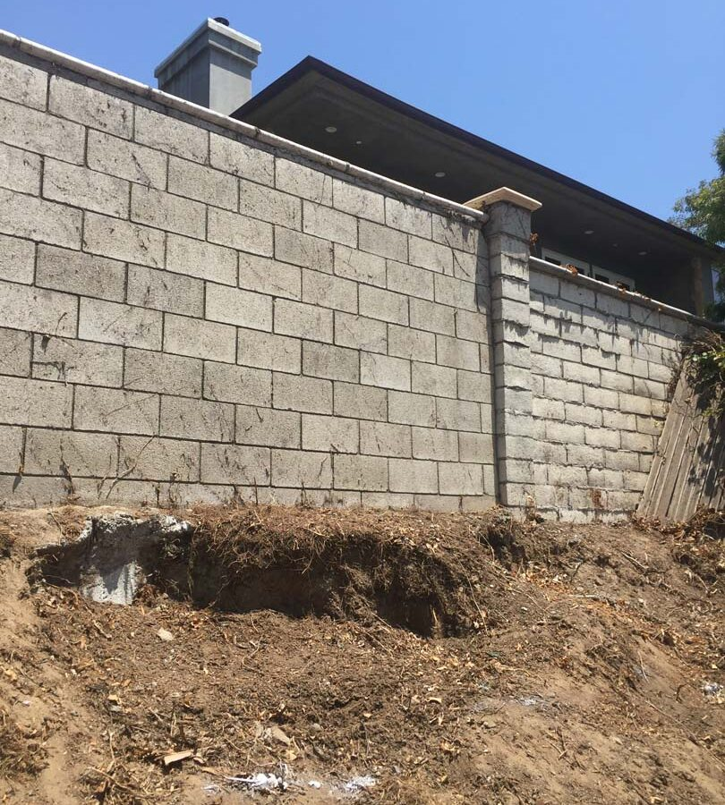 Old sloped hill where a new retaining wall will be built to create more flatspace in the backyard and safety. The freestanding wall's footing began to get exposed and this worried our client so he took action by calling us for a new retaining wall. Pacificland Constructors