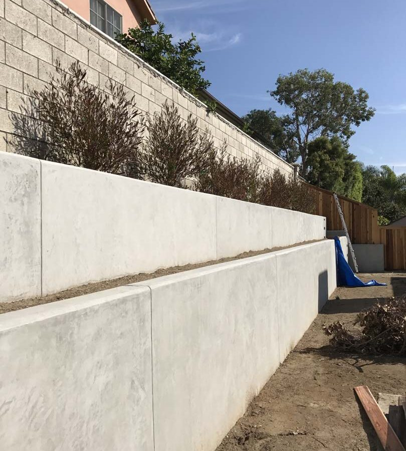 New pour in place concrete retaining wall for a backyard in Huntington Beach, CA. This retaining wall creates more flat area for the home because it holds up the differential earth elevation from the neighbor's home. It also creates a planter for vegetation. Pacificland Constructors