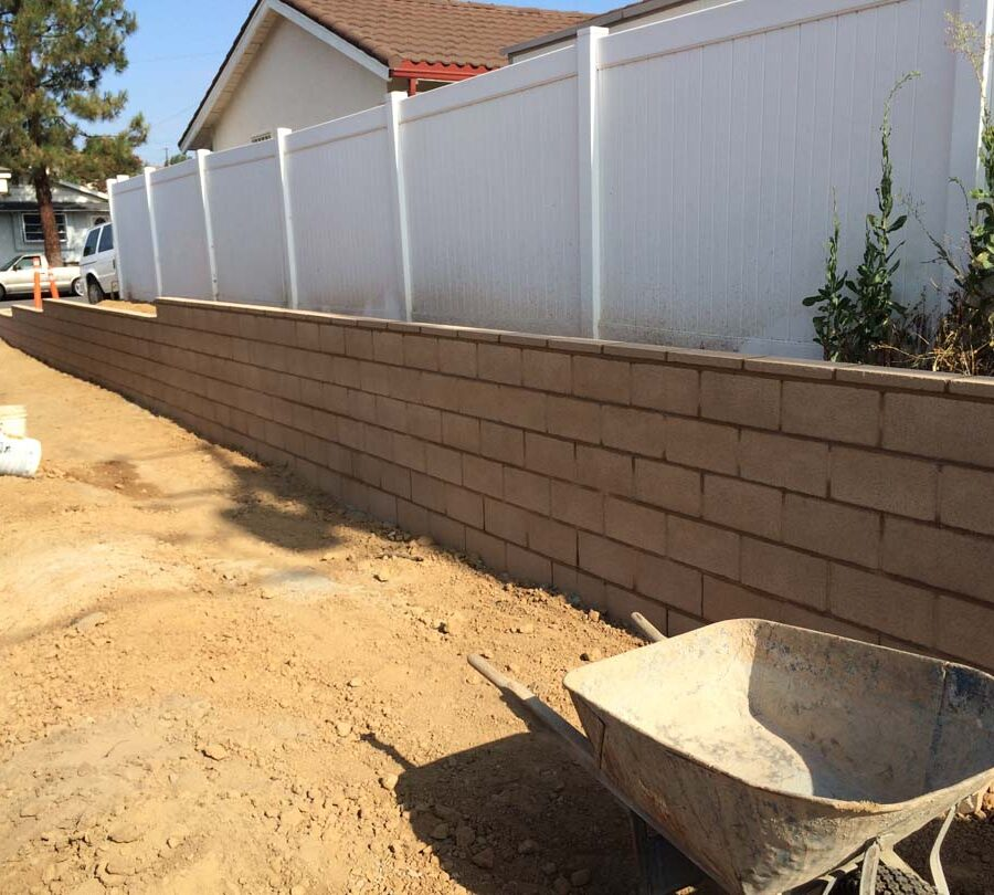 Construction for a new tan precision block retaining wall. Pacificland Constructors