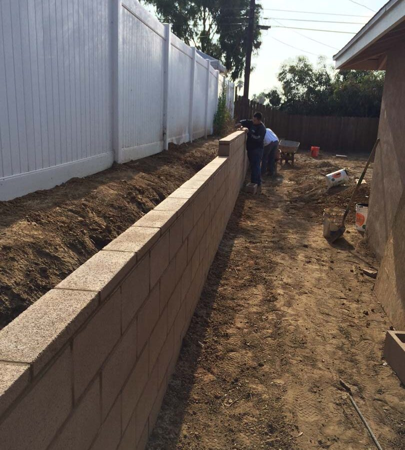 Laying a block wall caps for a new tan precision block retaining wall. Pacificland Constructors