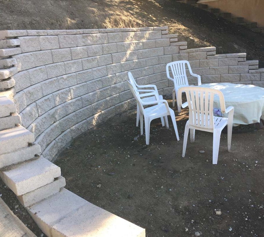 Small retaining wall intended to create flat area for the owner. Pacificland Constructors