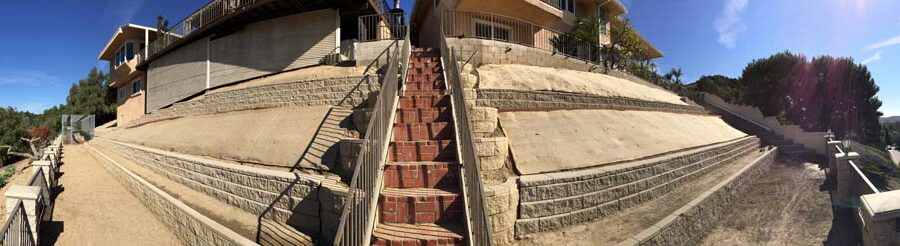 Panoramic view of new cmu retaining walls and brick steps. Pacificland Constructors