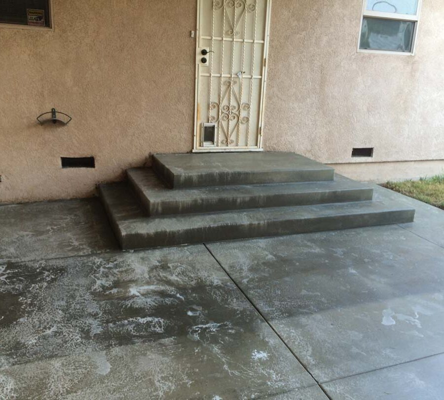 New beautiful broom swept concrete steps and backyard patio with a sealer polymer being applied to it. This polymer will become transparent when dry and protect the concrete from stains while creating a somewhat reflective surface as if it were just watered. Pacificland Constructors