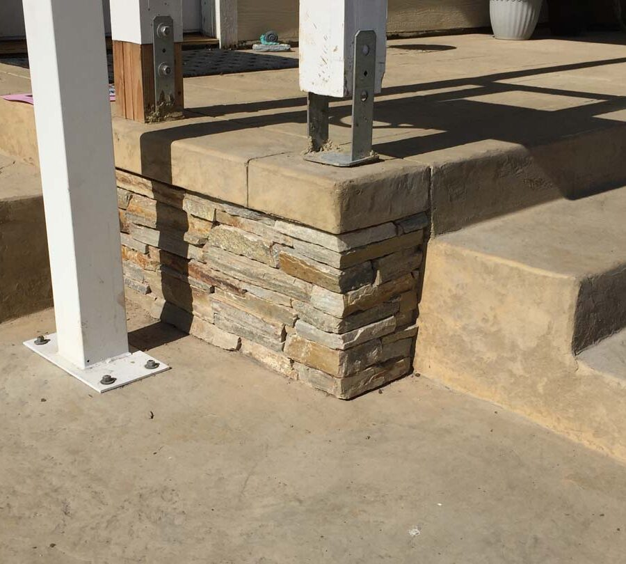 Colored stamped concrete with handmade joints. The steps also have the stamped texture and the porch face has stone veneer. Pacificland Constructors