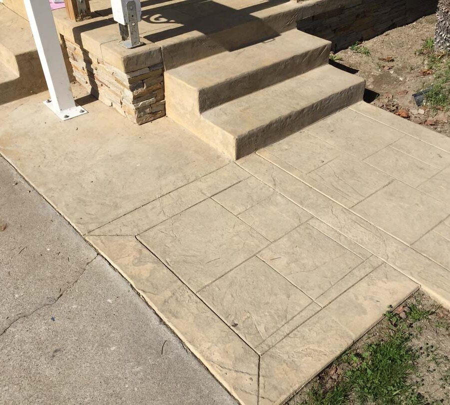 Colored stamped concrete with handmade joints. The steps also have the stamped texture and the porch face has stone veneer.