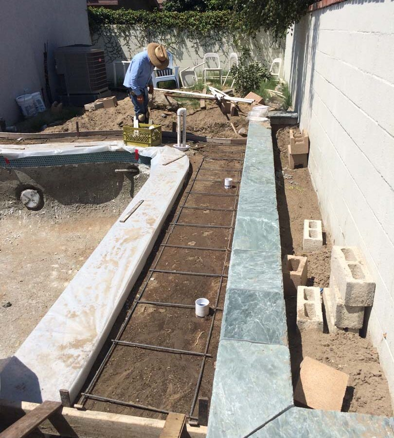 Steel reinforcement and pouring of a new gray concrete deck. We installed a water drainage system to make sure any rainfall or excess water drains out quickly to avoid slipping when using the pool. Pacificland Constructors